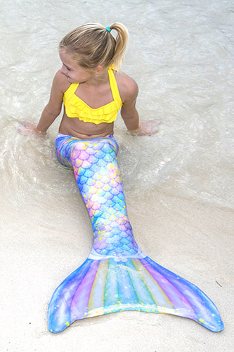 a young mermaid sits in the sand wearing the sweet dreams limited edition mermaid tail