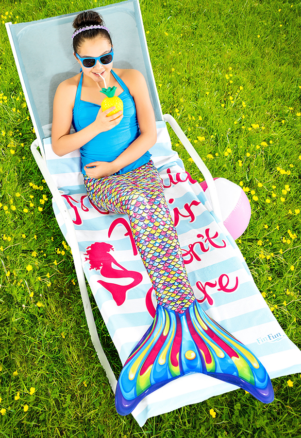 a mermaid lounges on a pool chair with a drink to portray the VIP treatment fin fun ambassadors receive