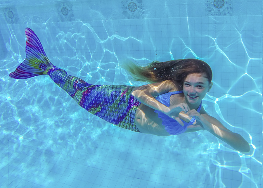 a mermaid swimming underwater making a heart with her hands