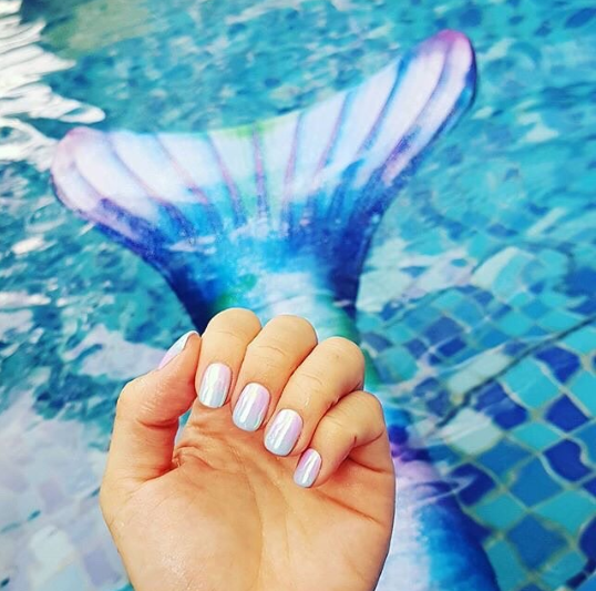 someone holding up their mermaid nails that match their mermaid tail by the pool