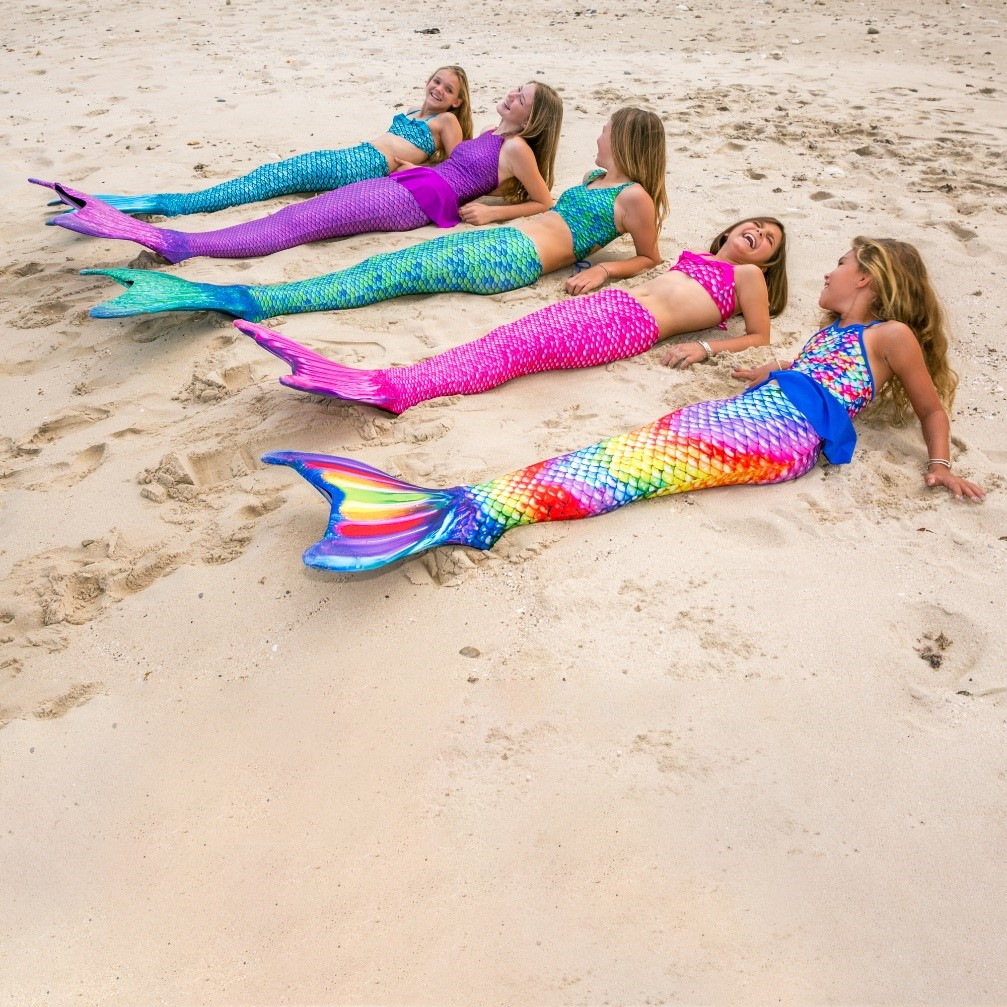 mermaids of all ages laying on the beach for a mermaid meetup