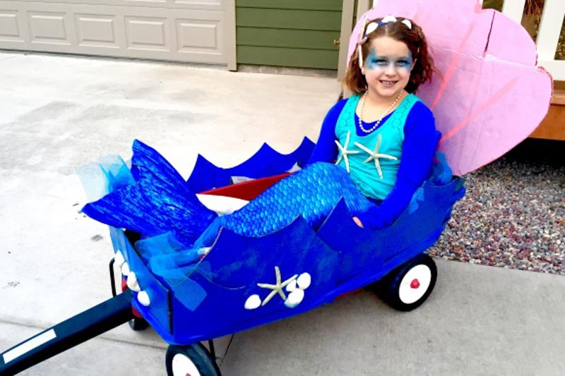 a young girl in the Arctic Blue mermaid tail riding in a sea-themed wagon
