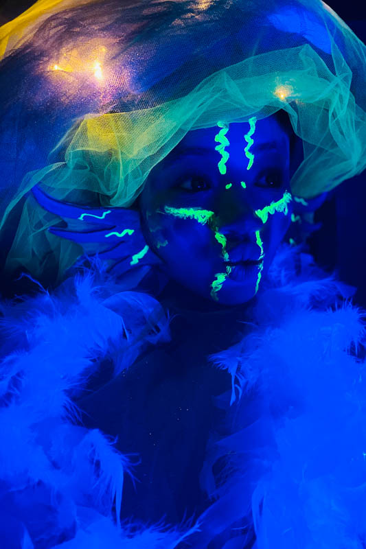girl dressed as a glowing sea creature under a black light
