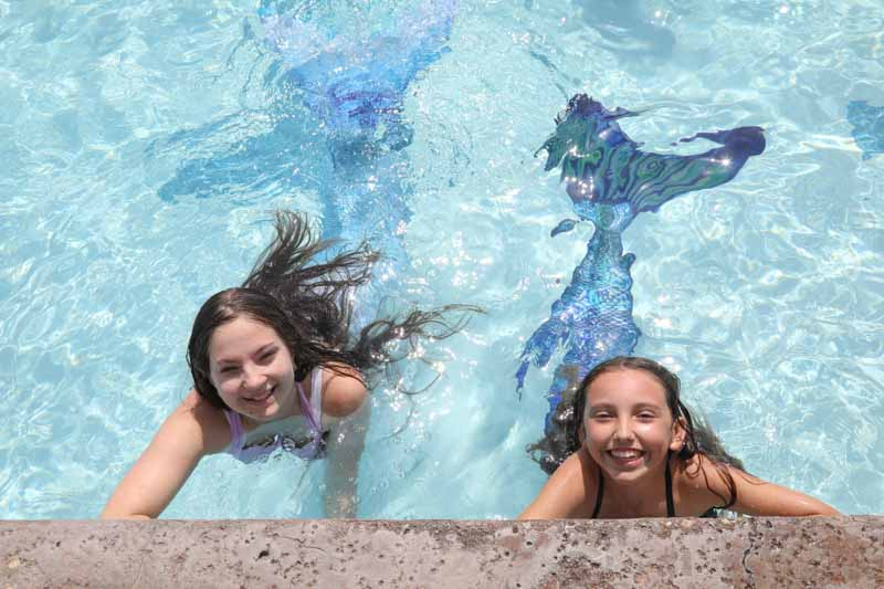 two happy girls swimming in mermaid tails