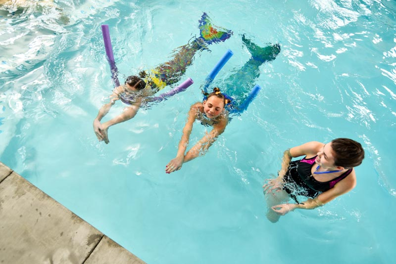 girls practicing mermaid tail swimming at a mermaid university class