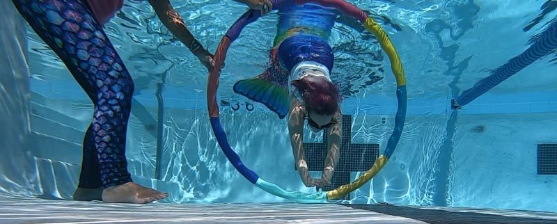 Molly swimming through hoops in her mermaid class.
