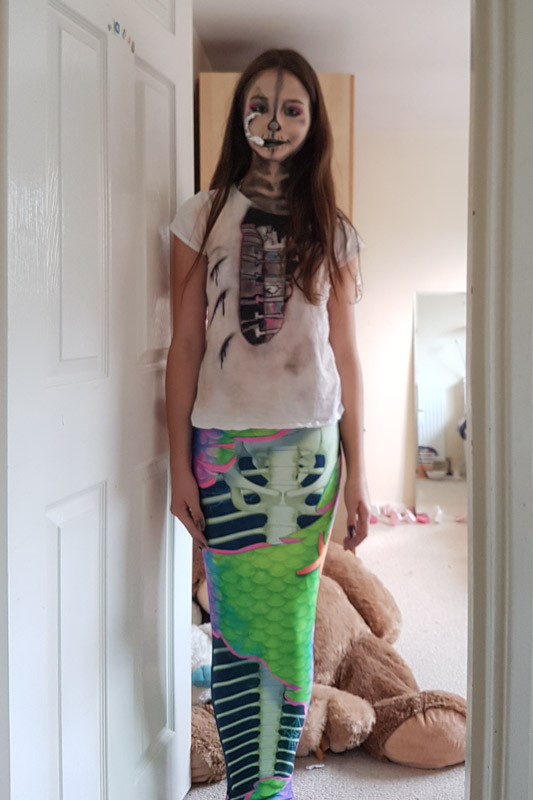 a girl dressed as a zombie mermaid with the Neon Skeletail mermaid tail for swimming