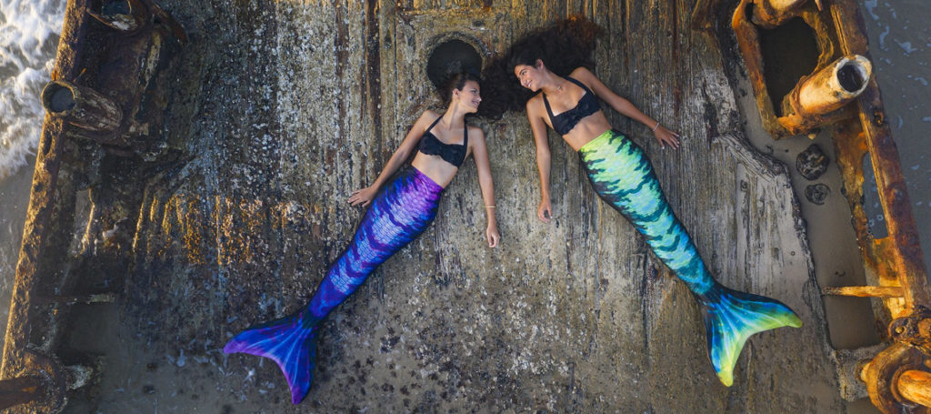 Two girls laying on a ship deck wearing the Hip Flip swimmable mermaid tail. One shows the purple side and the other shows the green and blue side.