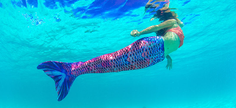 A girl swimming in the Sea Glass mermaid tail.