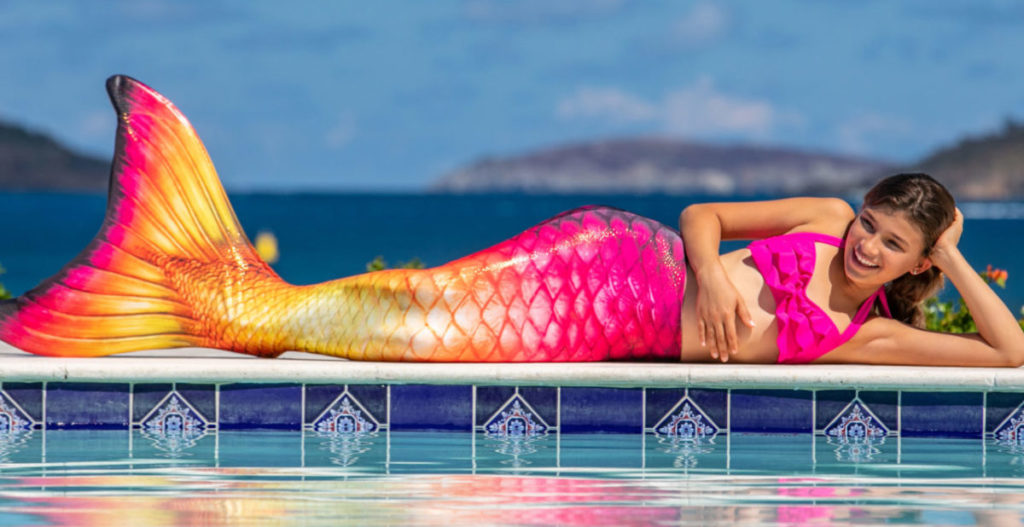 A girl laying next to the water in the Hawaiian Sun tail skin.