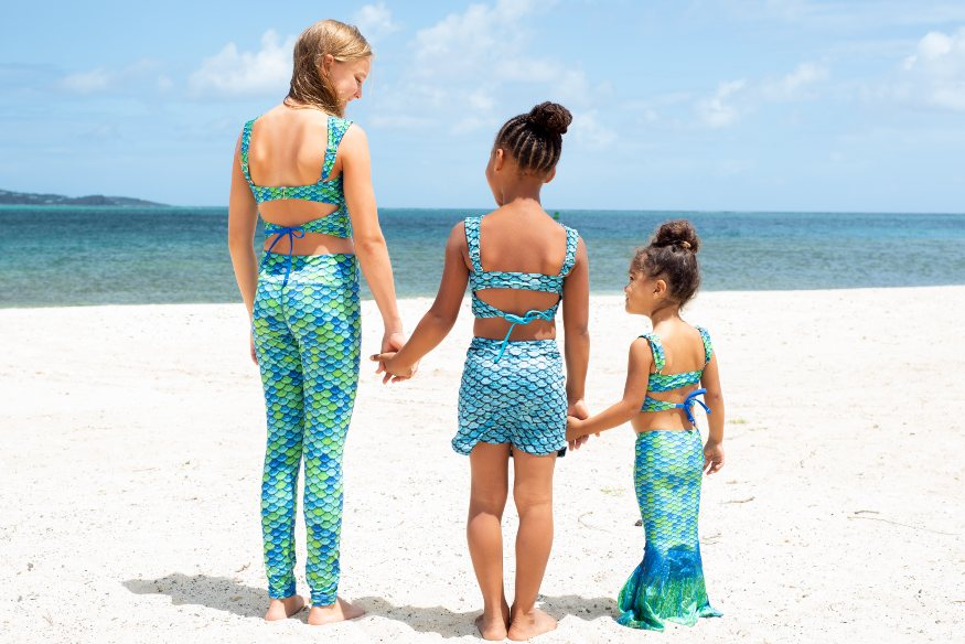 three girls in Fin Fun Mermaiden swimwear on a beach