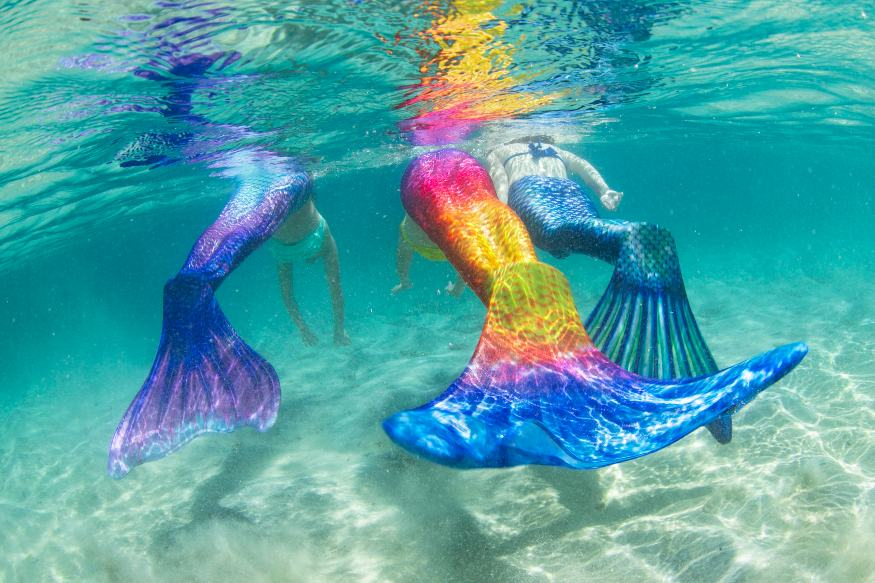 three girls swimming underwater in Fin Fun Limited Edition mermaid tails