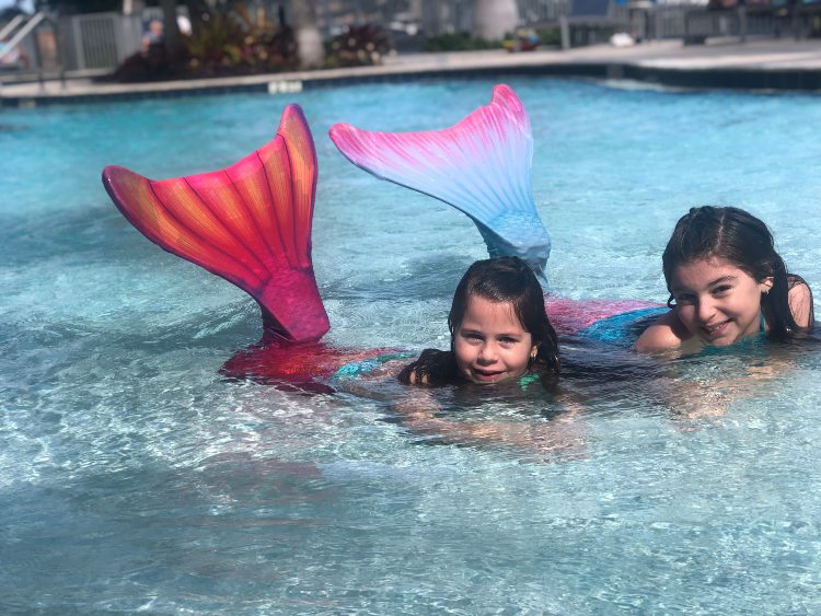 two girls posing in their swimmable mermaid tails in a pool