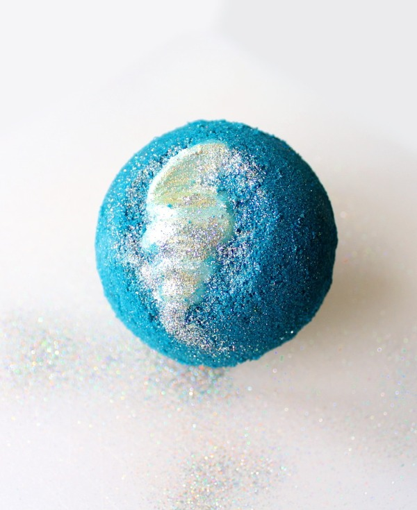 a blue bath bomb with a cocoa butter shell inside