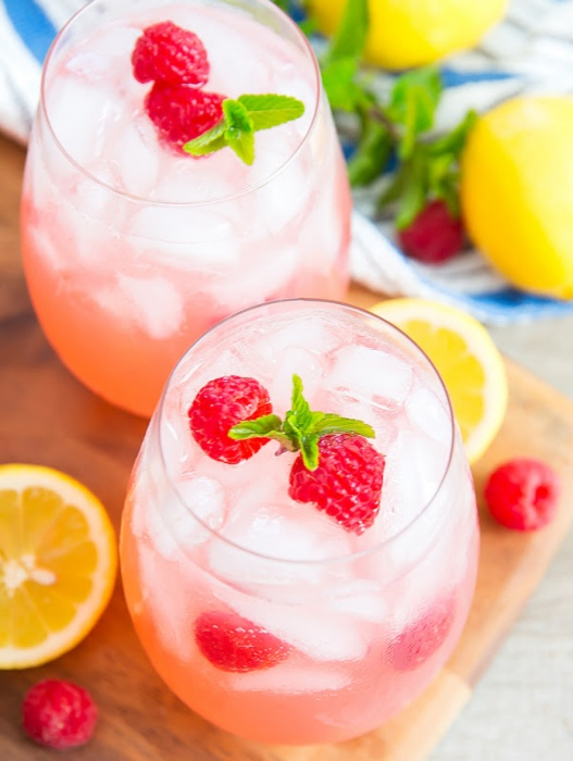 sparkling pink lemonade drink in two glasses with fresh raspberry and mint garnish