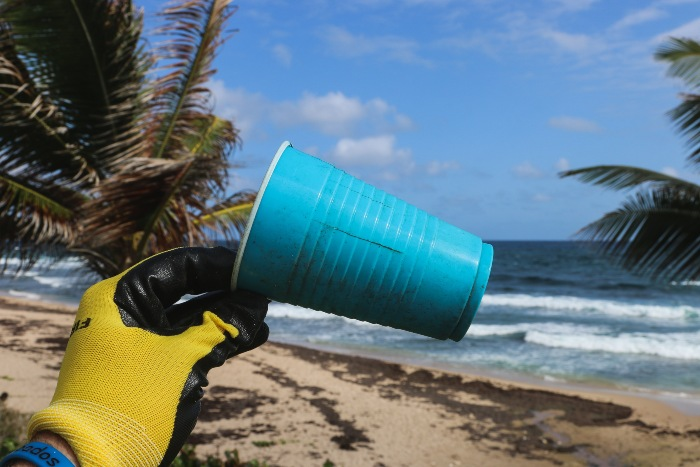 person holding up a plastic cup that was found on the beach
