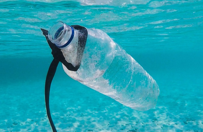 a discarded plastic water bottle floating in the ocean