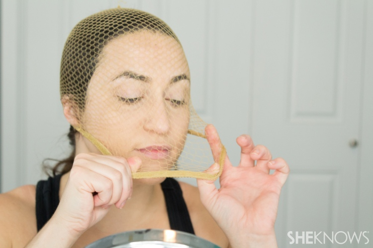 woman putting fishnets on her face to create a stencil for the mermaid scales