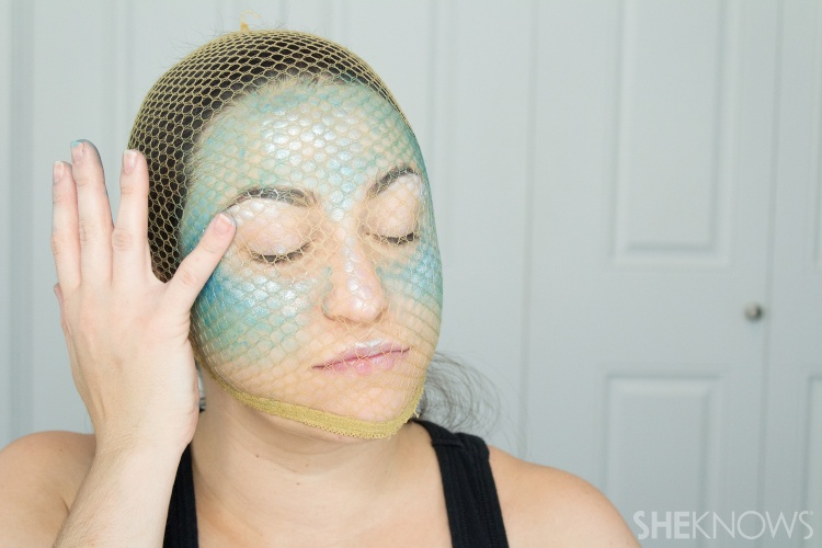 woman applying highlighter while wearing fishnets on her face