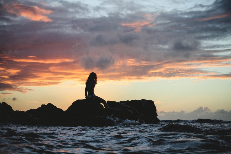 mermaid silhouette sitting on rocks in the ocean