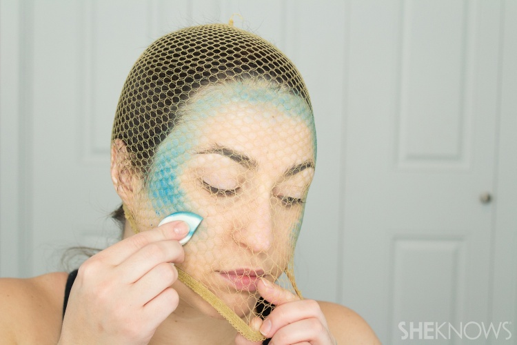 woman applying mermaid makeup with fishnets