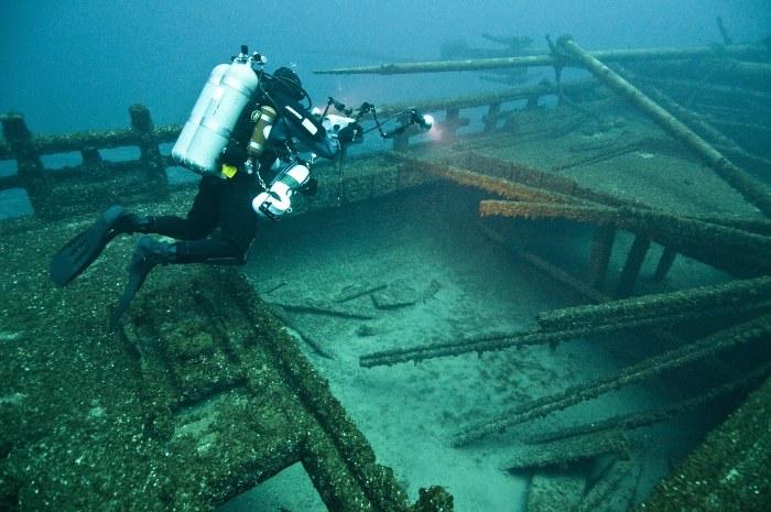 a scuba diver examining a shipwreck underwater
