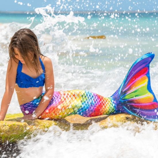 girl on a rock in the Rainbow Reef Mermaidens tail with waves crashing around her
