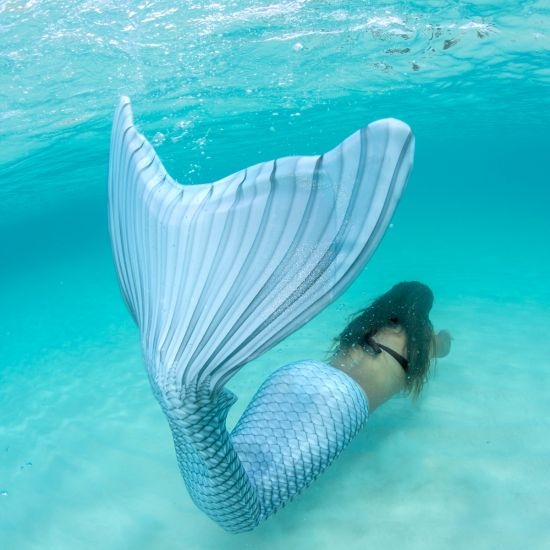 girl swimming underwater in the mermaid tail that matches April's birthstone, the Silver Lightning Limited Edition tail