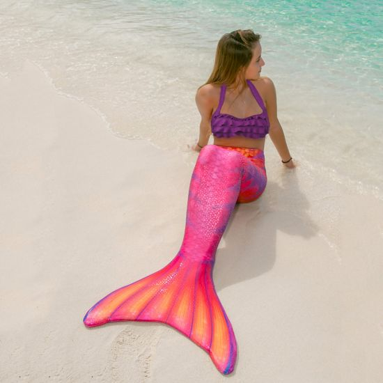 girl  on the beach wearing the Tiger Lily Limited Edition mermaid tail, which matches January's birthstone