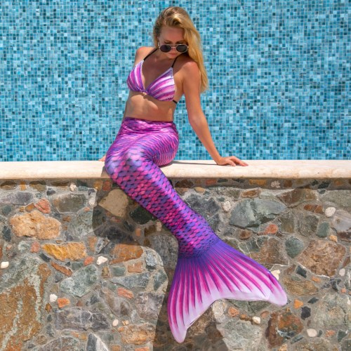 a woman sitting on a wall and spending her summer in a mermaid tail