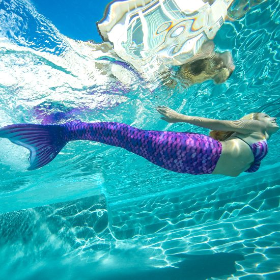 girl swimming underwater in a purple mermaid tail