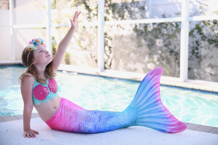 a young girl poses at the edge of the pool while wearing the Fiji Fantasy mermaid tail