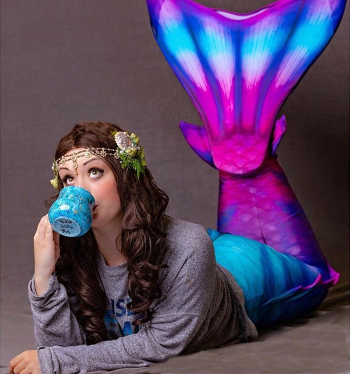 girl sipping from a mug while wearing a Fin Fun Atlantis mermaid tail