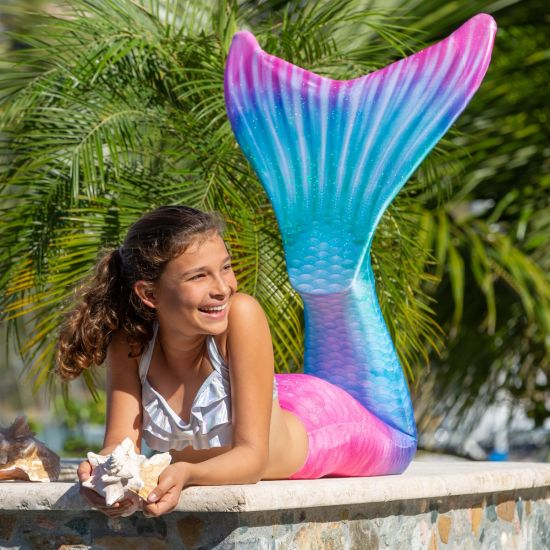 girl with natural hair wearing a Fin Fun mermaid tail and holding a seashell
