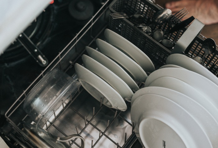 someone filling up a dishwasher