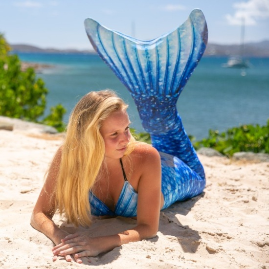 a girl in a blue mermaid tail lays on the beach and stares off into the distance with a serious face