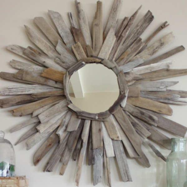 a sunburst mirror made with pieces of driftwood radiating from the center