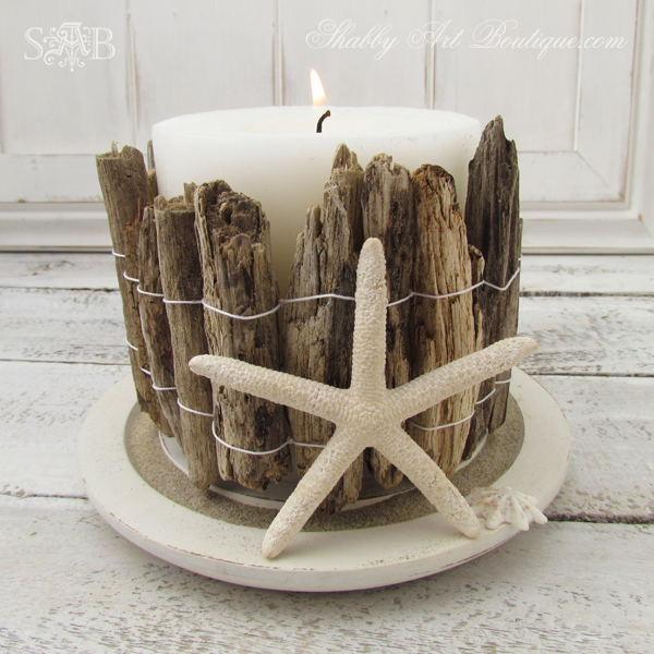 a white candle in a decorative DIY driftwood candle holder