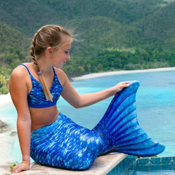 a girl poses next to the pool in a sapphire-blue mermaid tail