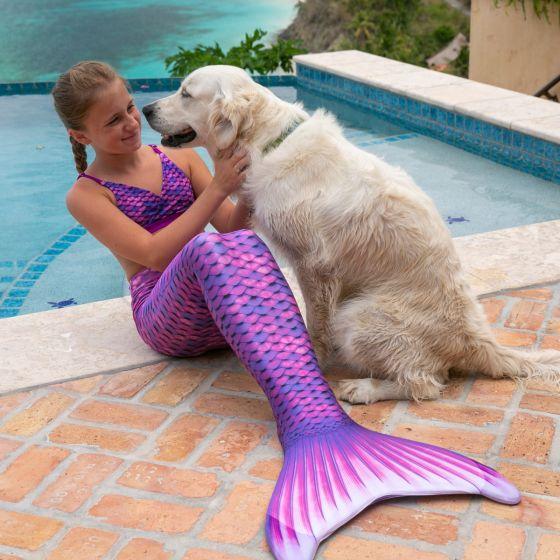 girl in the Asian Magenta mermaid tail and scale bikini petting a dog