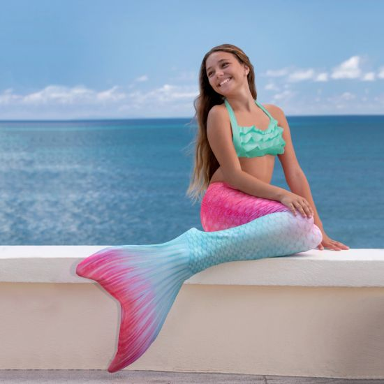 girl in the Bahama Blush Fin Fun mermaid tail sits on a ledge with the ocean in the background