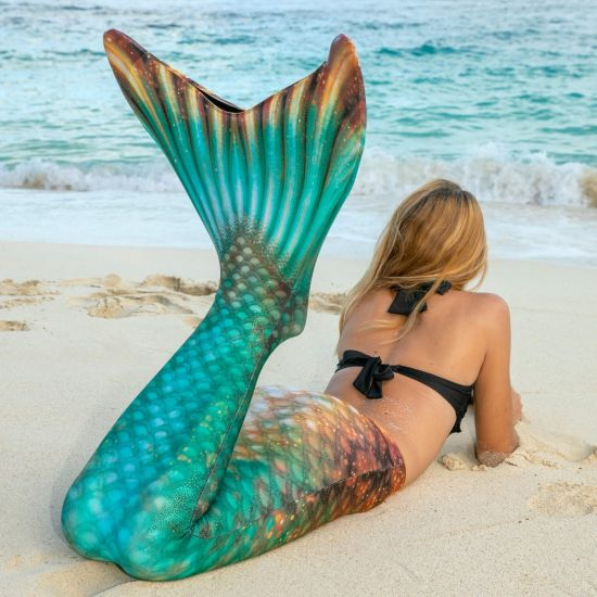girl laying in the sand in the Bronzed Emerald Limited Edition mermaid tail