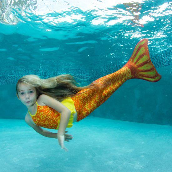 girl swimming underwater in the orange and yellow Tropical Sunrise mermaid tail