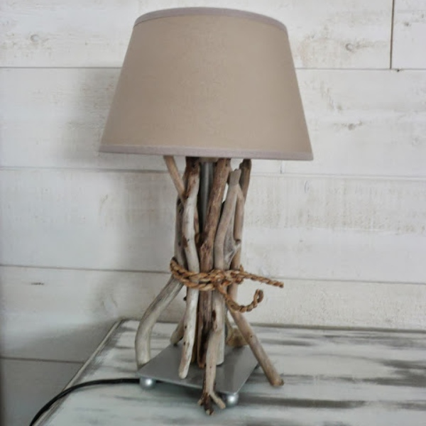 a plain lamp decorated with driftwood and rope