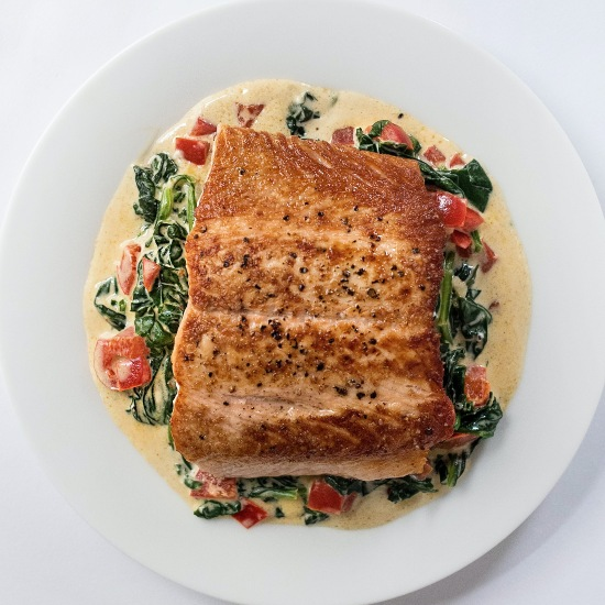 a beautiful plate of fish florentine from above: seared fish on a creamy sauce with spinach and pepper