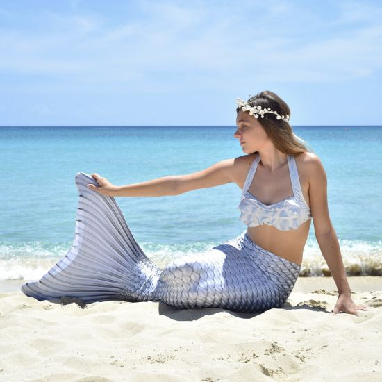girl in a silver bikini and mermaid tail wearing a white headpiece
