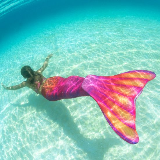 girl swimming underwater in a bright pink and orange mermaid tail