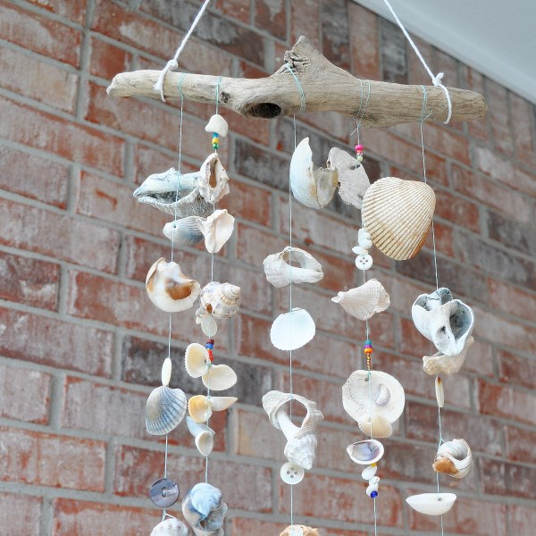 a wind chime made with driftwood, sea shells, buttons, and beads hanging in front of a brick wall