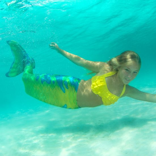 girl swimming on her side underwater in a yellow, green, and blue mermaid tail