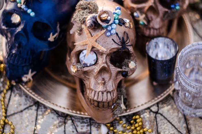 gold and blue decorative skulls covered in starfish, shells, spiders, moss, and gems